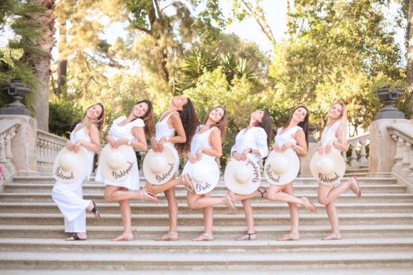 7 copines en robes blanches avec des chapeaux de paille dans un parc en espagne