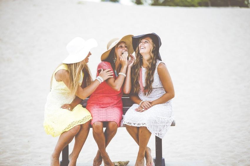 trois copines qui rigolent sur un banc a la plage