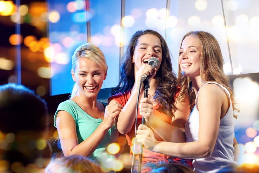 trois filles qui chantent ensemble devant un micro